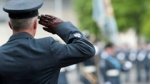 A Royal Air Force Station Warrant Officer salutes the Old Colours at a Parade.